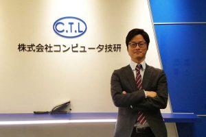 コンピュータ技研のロゴ前にたつ園田さん