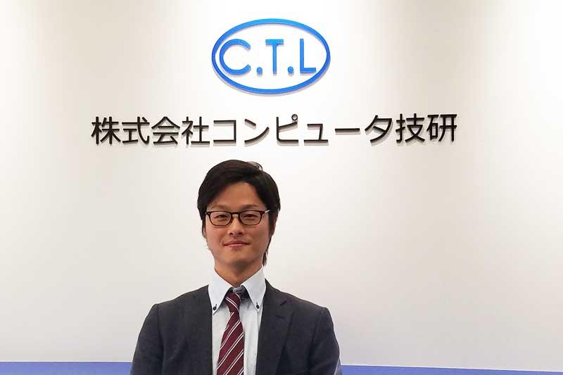 NextC.T.L社員インタビュー コンピュータ技研ロゴ前にたつ園田さん